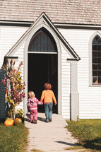 kids holding hands in front of a church door in fall