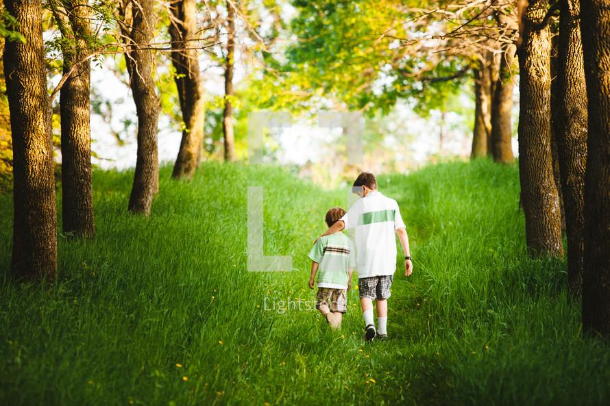 brothers walking through green grass