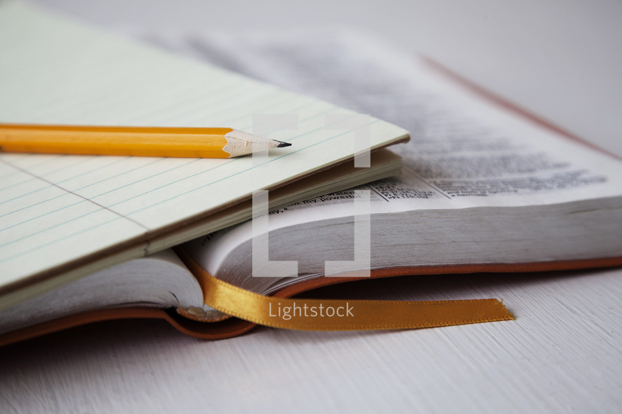 pencil, notepad, and open Bible