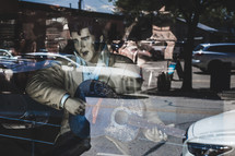 reflection of a statue of Elvis playing a guitar in a window