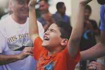 A little boy raises his arms after being baptized.