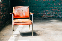 Chair in en empty room with brick walls.