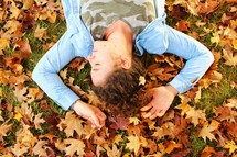 girl lying in fall leaves