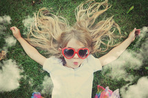 a girl in sunglasses lying in grass