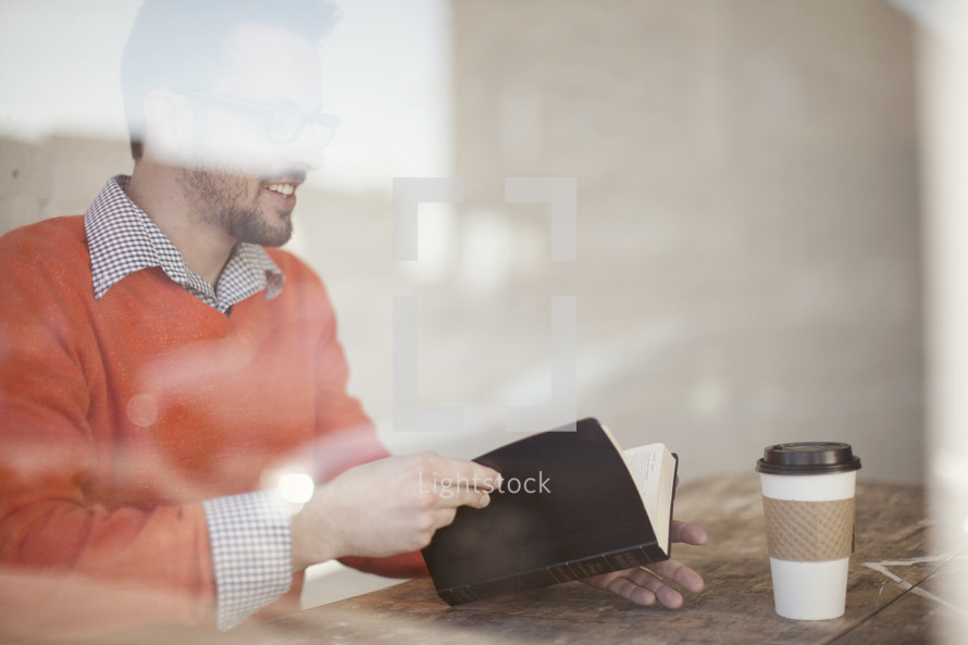 blurry image of a man reading the Bible and a coffee cup
