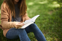 a woman sitting in the grass reading a Bible