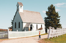 child running towards a small white church