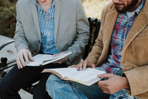 two men reading scripture sitting on a park bench