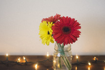 gerber daisies in a mason jar on a wooden table