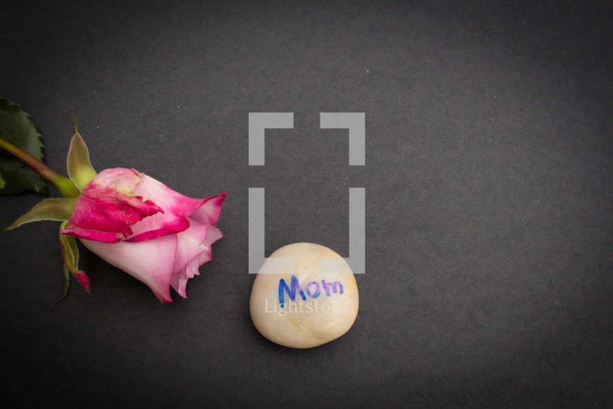 pink rose and stone with word mom