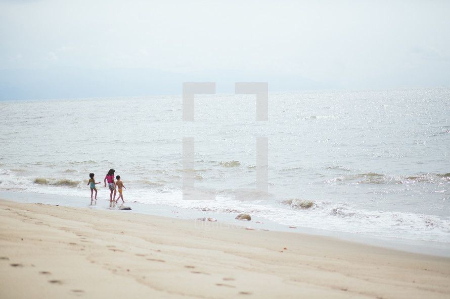 a family on the beach playing in the water