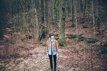 A woman standing alone in a forest