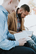 two men reading a Bible and discussing scripture while sitting on a park bench