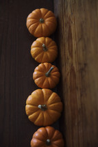 row of orange pumpkins on wood