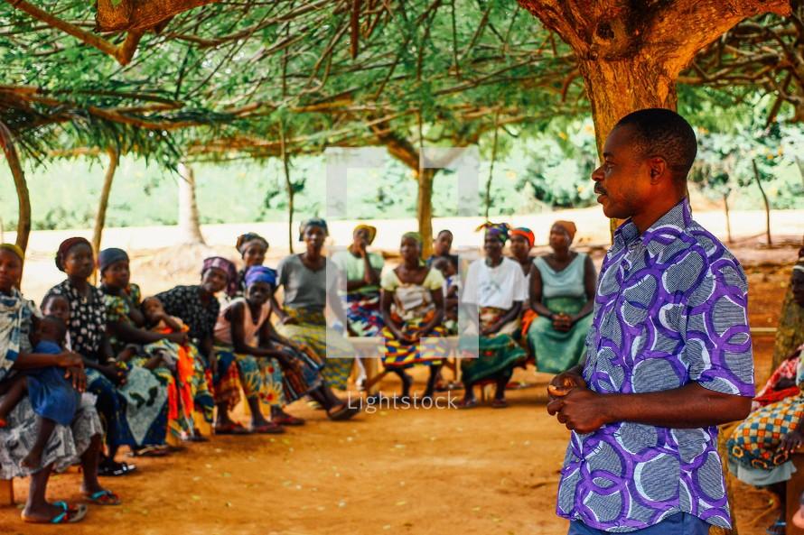 man speaking to women in a village