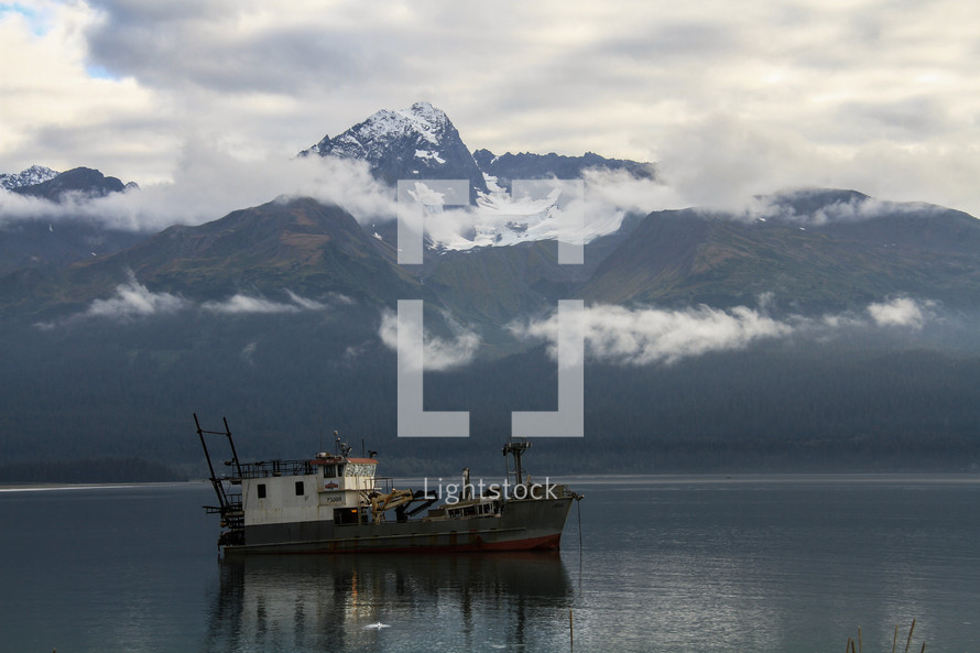 fishing boat on calm water and mountain view