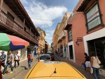 pedestrians and cars on a narrow street