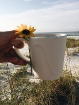 yellow flower and coffee mug on a beach