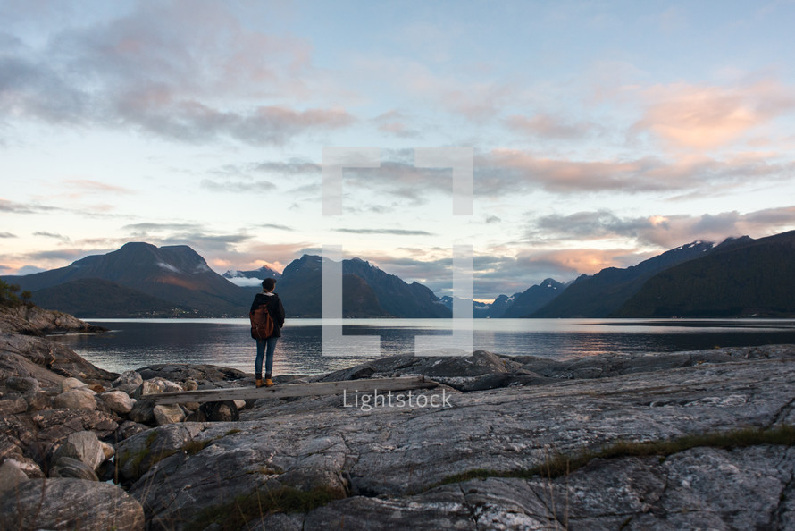 A solitary hiker standing on a rocky shore and gazing out over a lake with mountains beyond.