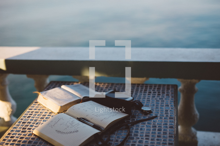 open Bible, journal, pen, phone, and watch on a table outdoors