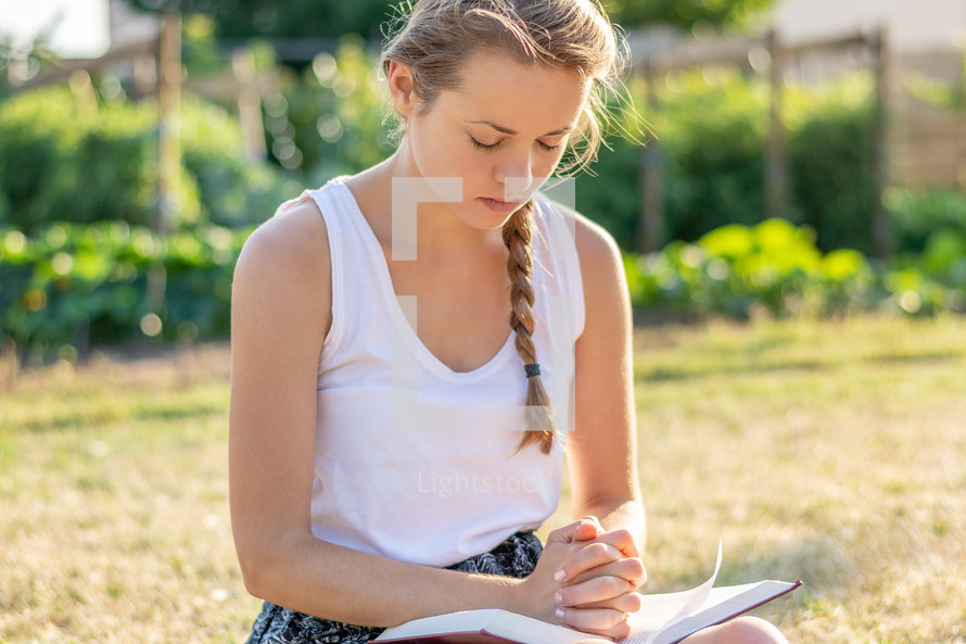 a woman reading a Bible outdoors and praying