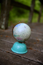 globe on a weathered boardwalk