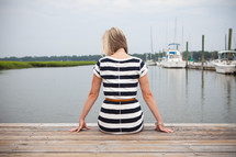 woman sitting at the end of a dock