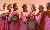 Buddhist novices in traditional pink dress carrying begging bowls