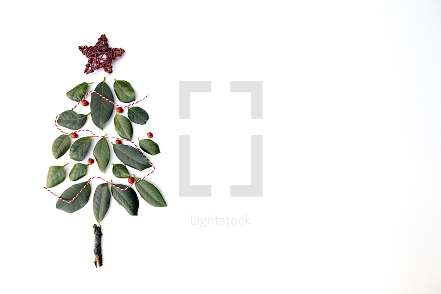simple Christmas tree of leaves and string on a white background with copy space