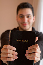 Man holding out a Holy Bible