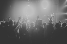 Silhouette of an audience with raised hands worshiping at a concert.