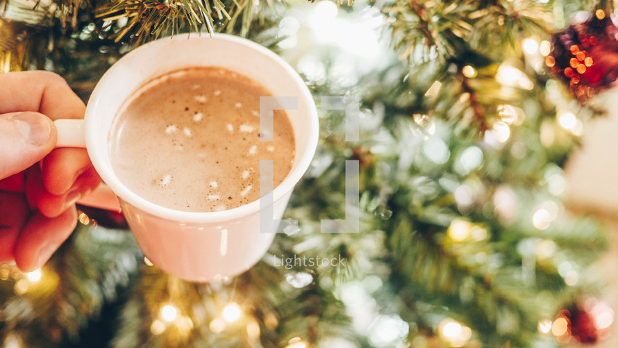 hand holding hot chocolate in front of a Christmas tree