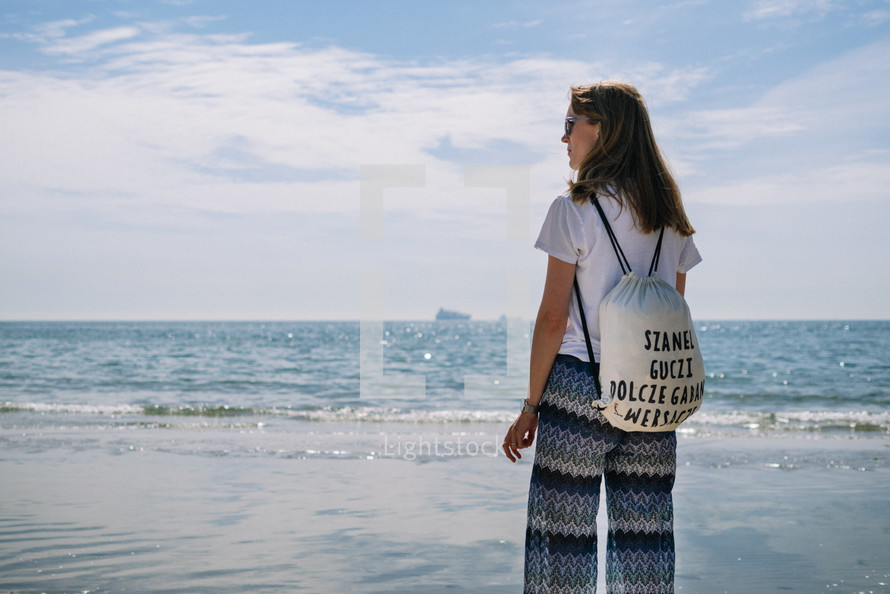 a woman standing on a beach looking out at the ocean