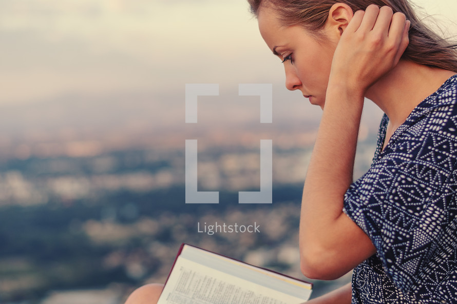 a young woman reading a Bible