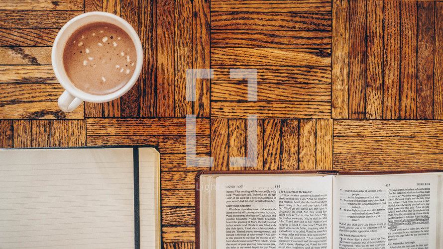 journal, open Bible, and hot cocoa on a table