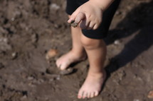 toddler standing in mud
