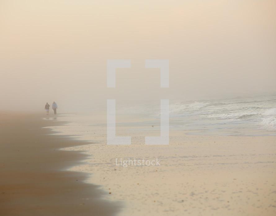 people walking on a beach in fog