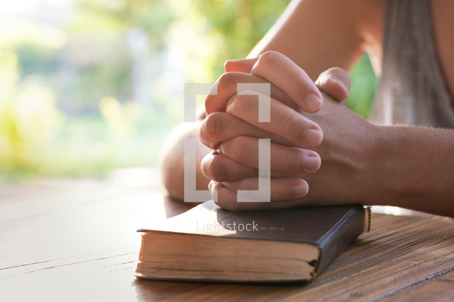 praying hands on the cover of a Bible