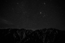 stars in a night sky above a mountain