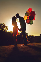 couple holding balloons at sunset