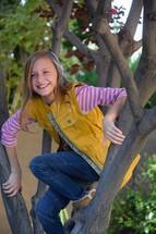 a preteen girl climbing a tree