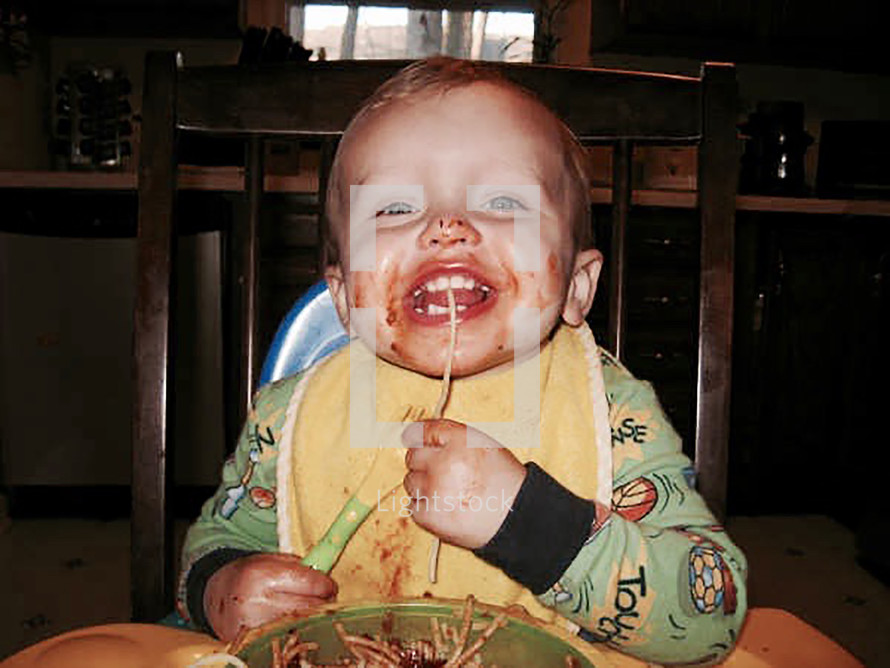 A messy toddler boy eating spaghetti in a high-chair