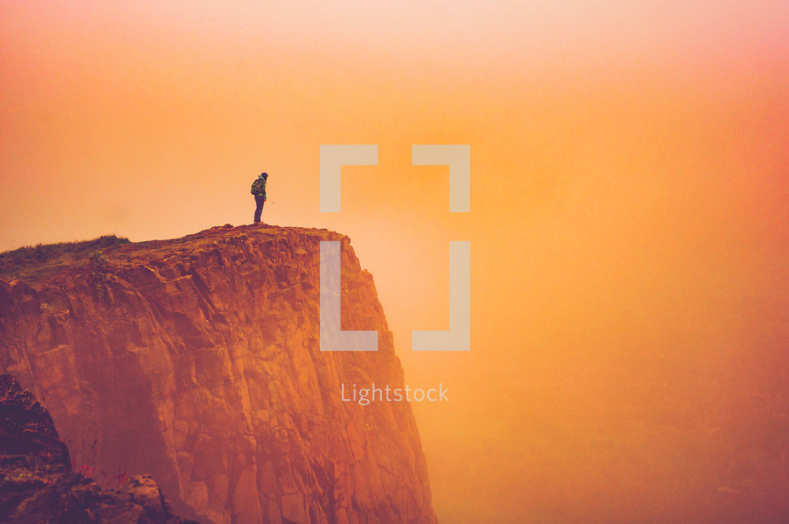 man standing at the edge of a cliff under an orange sky