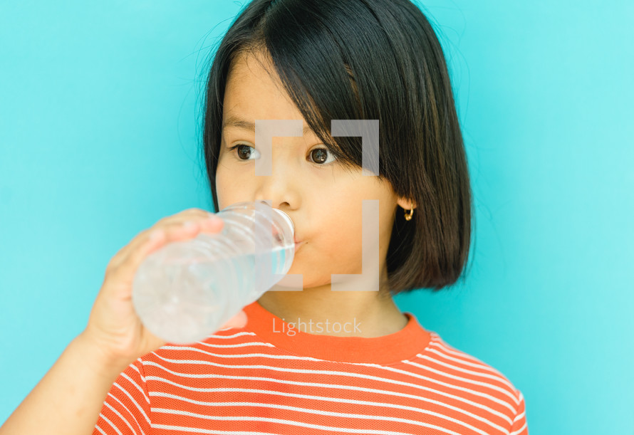 girl drinking from a water bottle