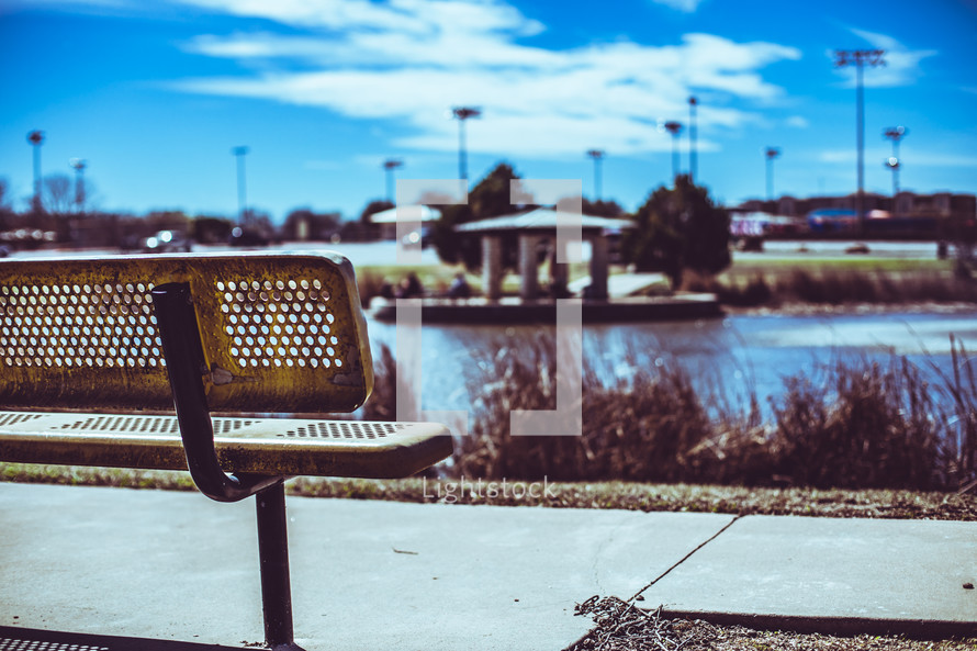park bench with a view of a pond