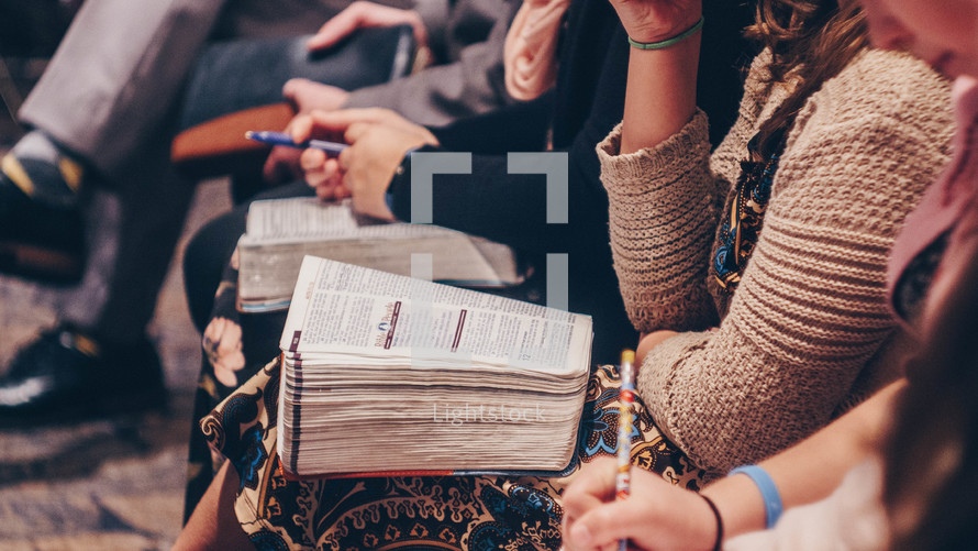 parishioners with Bibles in their laps at church