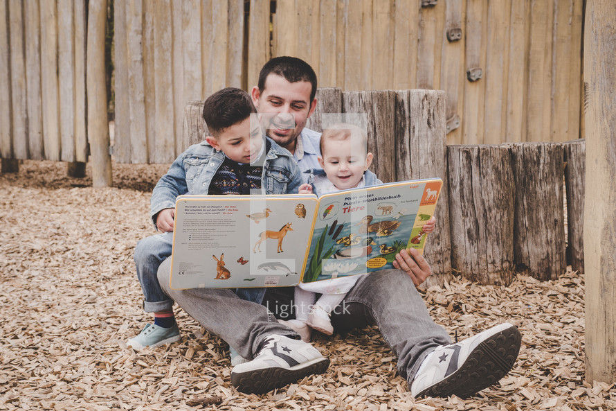 father reading a book to his kids