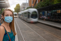 a woman wearing a face mask at train station