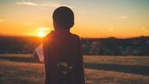 Boy facing the sun, putting on a superman cape.