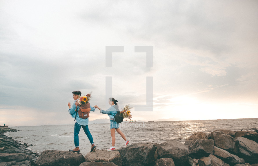 a couple holding hands walking on a rock jetty at a shore